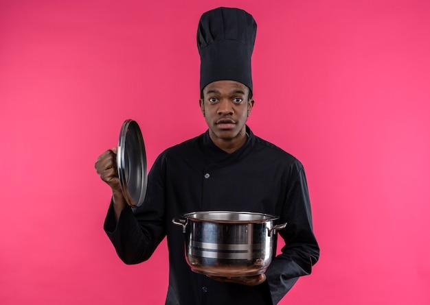 シェフの制服を着た若い気になるアフリカ系アメリカ人の料理人は鍋を保持し、コピースペースでピンクの背景に分離されたカメラを見ます 無料写真