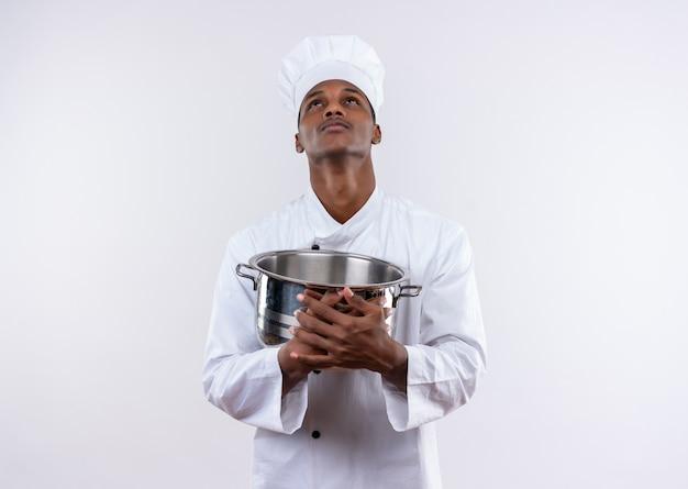 シェフの制服を着た若い気になるアフリカ系アメリカ人の料理人は鍋を保持し、コピースペースで孤立した白い背景を見上げます 無料写真