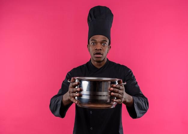 シェフの制服を着た若い気になるアフリカ系アメリカ人の料理人は、コピースペースでピンクの背景に分離された鍋を保持します 無料写真