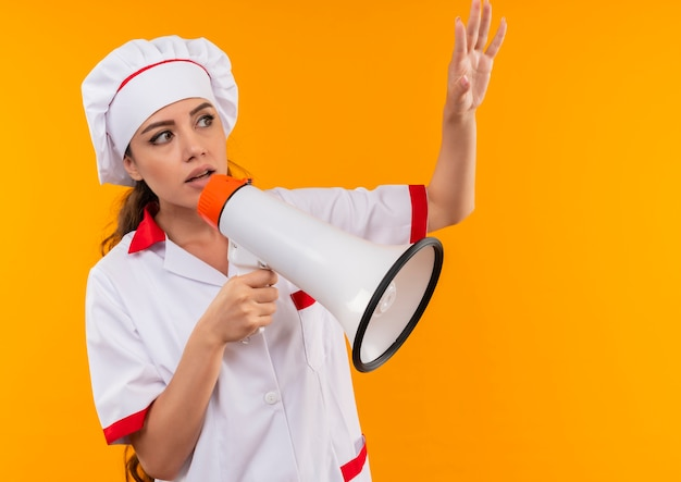 シェフの制服を着た若い気になる白人料理人の女の子は、大きなスピーカーを保持し、コピースペースでオレンジ色の背景に分離された手を上げます 無料写真