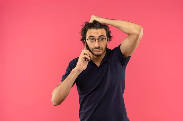 光学メガネをかけた黒いシャツを着た若い不安な男が電話で話し、ピンクの壁に隔離された頭を保持します。 無料写真