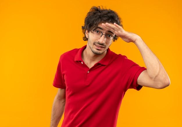 光学ガラスの赤いシャツを着た若い不安な男は、オレンジ色の壁に遠く離れた何かを見ようと額に手のひらを保ちます 無料写真