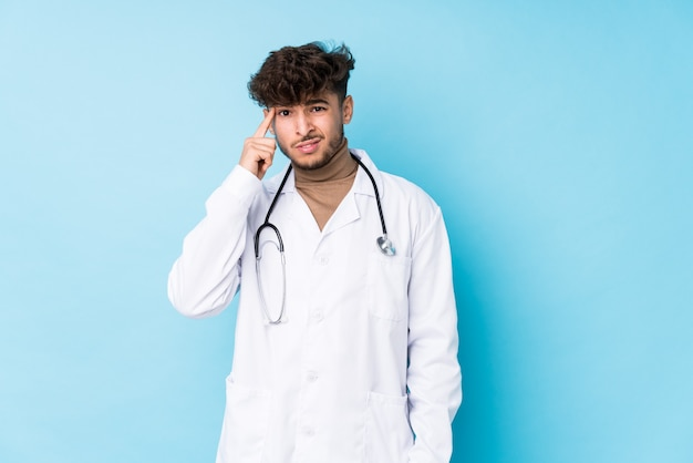 Young arab doctor man idolated showing a disappointment gesture with forefinger. Premium Photo