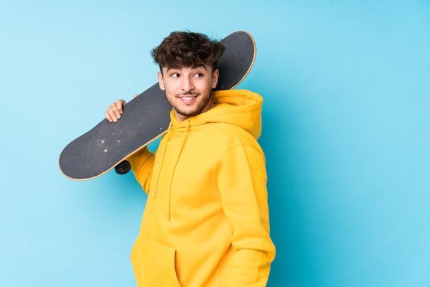 Изолированный молодой арабский фигурист смотрит в сторону улыбающегося, веселого и приятного. Premium Фотографии