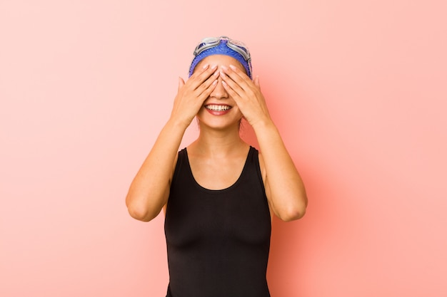 Young arab swimmer woman isolated covers eyes with hands, smiles broadly waiting for a surprise. Premium Photo