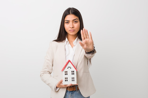 Young arab woman holding a house icon standing with outstretched hand showing stop sign, preventing you. Premium Photo