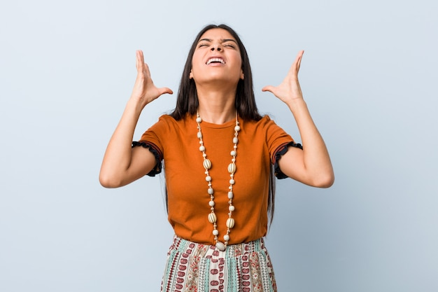 Young arab woman screaming to the sky, looking up, frustrated. Premium Photo