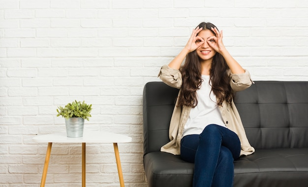 Young arab woman sitting on the sofa showing okay sign over eyes Premium Photo