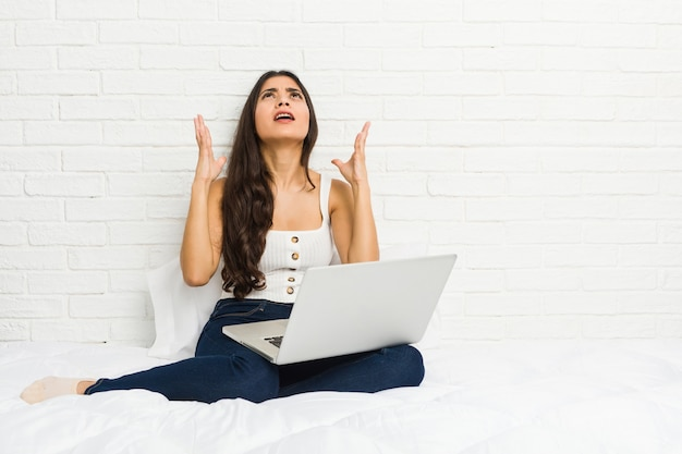 Young arab woman working with her laptop bed screaming sky, looking up, frustrated. Premium Photo