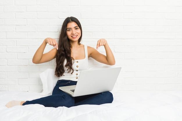 ベッドで彼女のラップトップで働く若いアラブ女性は、指、肯定的な感情で下向き。 Premium写真