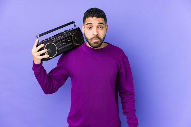 Молодой арабский человек, держащий изолированную радиокассету молодой арабский мужчина, слушающий музыку, пожимает плечами и смущенно открывает глаза. Premium Фотографии
