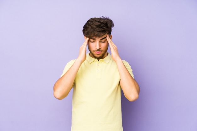 Young arabian man isolated on a purple wall touching temples and having headache. Premium Photo