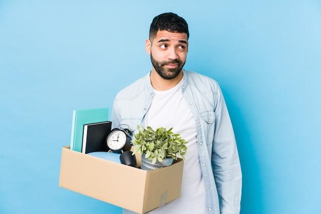 Молодой арабский мужчина переезжает в новый дом изолированно мечтает о достижении целей и задач Premium Фотографии