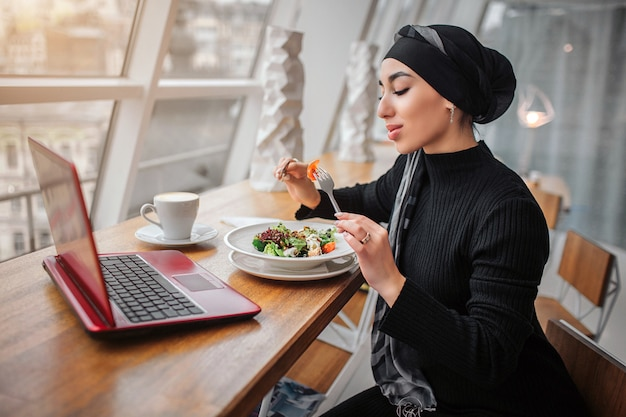 Young arabian woman sit at table in front of window Premium Photo