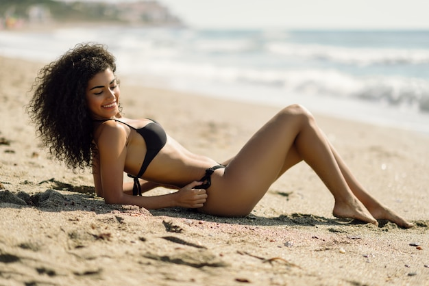 Young arabic woman with beautiful body in swimwear lying on the beach sand. Free Photo