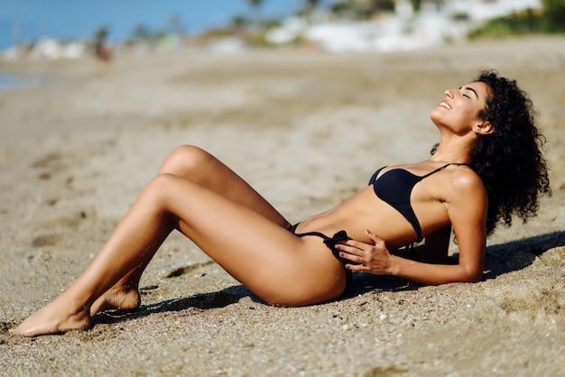 Young arabic woman with beautiful body in swimwear lying on the beach sand Free Photo