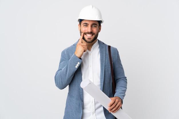 헬멧과 청사진을 들고 젊은 건축가 남자는 행복하고 즐거운 표정으로 웃고 흰색에 고립 프리미엄 사진