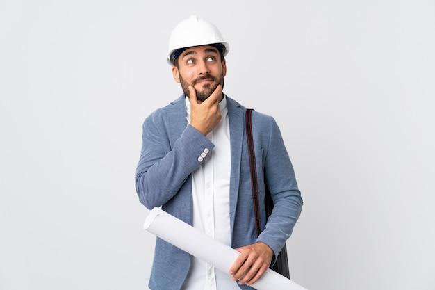 Молодой человек архитектора с шлемом и держать чертежи изолированные на белой стене думая идея пока смотрящ вверх Premium Фотографии