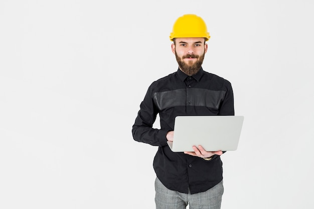 Young architect wearing yellow hardhat holding portable laptop Free Photo