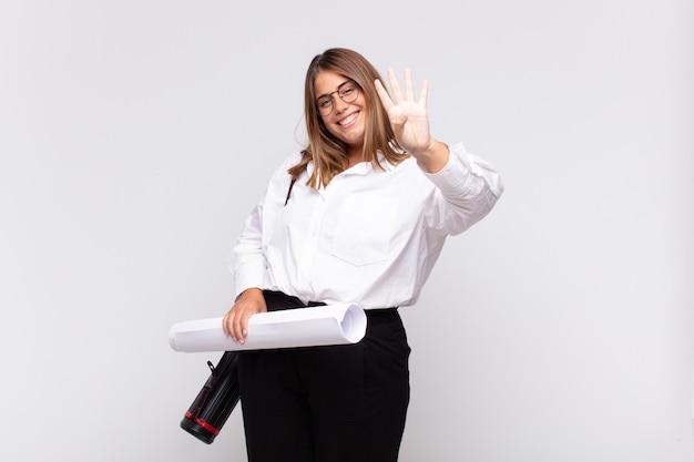 Молодая женщина-архитектор улыбается и выглядит дружелюбно, показывая номер четыре или четвертый с рукой вперед, отсчитывая Premium Фотографии