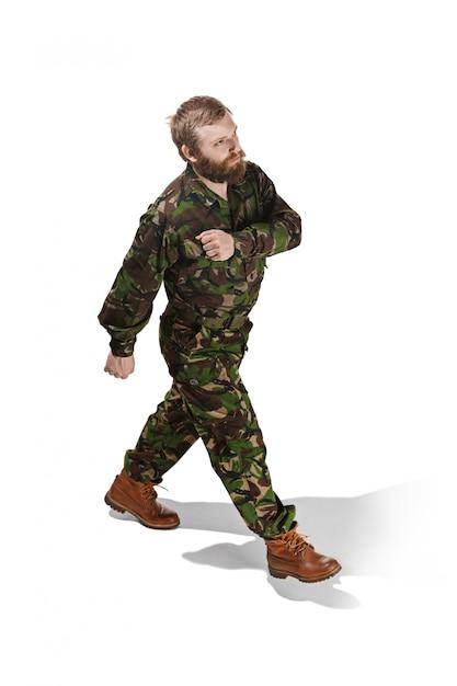 迷彩服を着た若い軍の兵士が白いスタジオに分離されて行く 無料写真