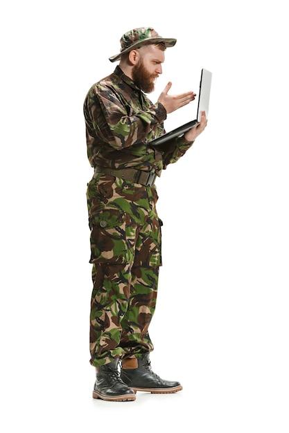 ノートパソコンとフルレングスの白いスタジオ背景に分離された迷彩服を着ている若い陸軍兵士。軍事、兵士、軍のコンセプトです。プロフェッショナル、コミュニケーション、コネクテッドピープルのコンセプト 無料写真