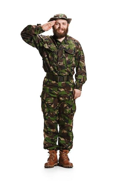 Giovane soldato dell'esercito che indossa l'uniforme del camuffamento in piedi e salutando isolato su sfondo bianco per studio a figura intera. giovane modello caucasico. militare, soldato, concetto dell'esercito. concetti professionali Foto Gratuite