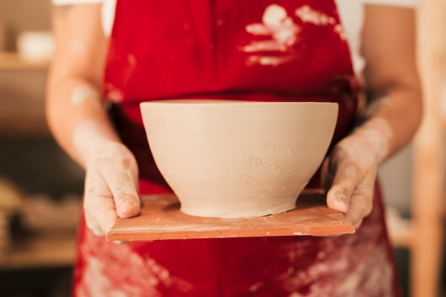 Young artisan hand showing a craft clay bowl on wooden tray Free Photo