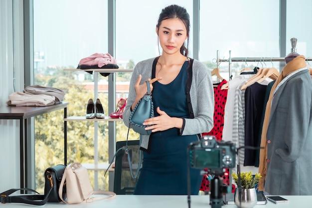 若いアジア美人ライブビデオブログとオンラインeコマースショッピングのセールスバッグ Premium写真