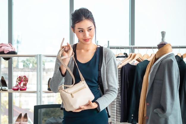 若いアジア美人ライブビデオブログ(vlogger)と洋服店でのオンラインeコマースショッピングのセールスバッグ。 Premium写真