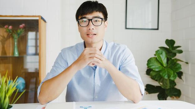Молодой азиатский бизнесмен, использующий компьютерный ноутбук, разговаривает с коллегами о плане во время видеозвонка, работая дома в гостиной. самоизоляция, социальное дистанцирование, карантин от вируса короны. Бесплатные Фотографии