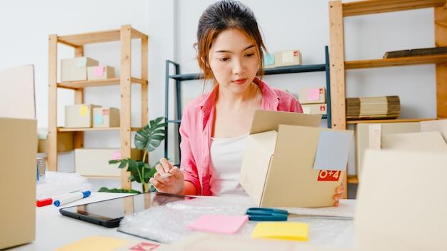 Молодой азиатский предприниматель-предприниматель проверяет заказ на покупку продукта на складе и сохраняет на планшетном компьютере работу в домашнем офисе. владелец малого бизнеса, доставка на рынок онлайн, внештатная концепция образа жизни. Бесплатные Фотографии