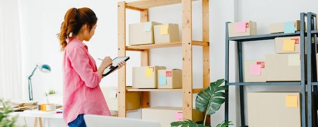 Giovane imprenditrice asiatica imprenditrice controlla l'ordine di acquisto del prodotto in magazzino e salva sul tablet che lavora in ufficio a casa. proprietario di una piccola impresa, consegna sul mercato online, concetto di freelance di stile di vita. Foto Gratuite