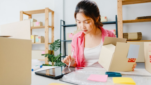 Young asia entrepreneur businesswoman check product purchase order on stock and save to tablet computer work at home office. small business owner, online market delivery, lifestyle freelance concept. Free Photo