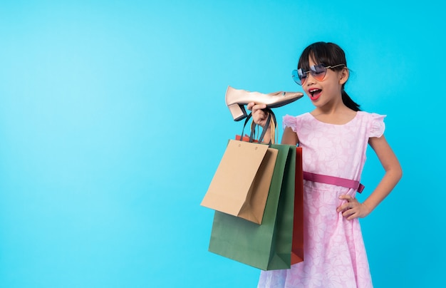 Young asia girl kid holding shoe with shopping bag Premium Photo