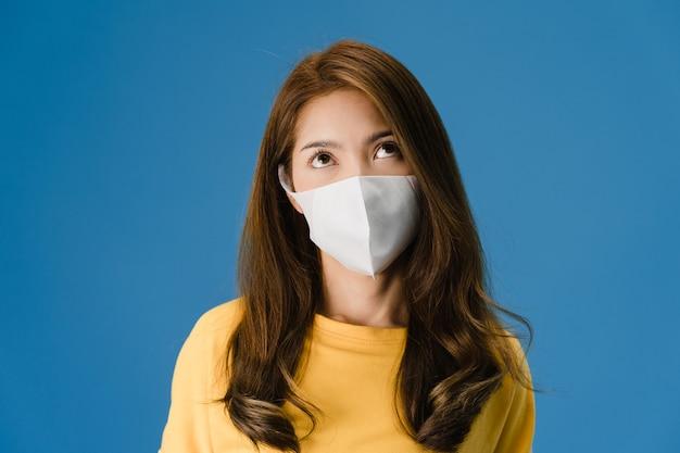 Молодая азиатская девушка в медицинской маске, уставшая от стресса и напряжения, уверенно смотрит в пространство, изолированное на синем фоне. самоизоляция, социальное дистанцирование, карантин для предотвращения вируса короны. Бесплатные Фотографии