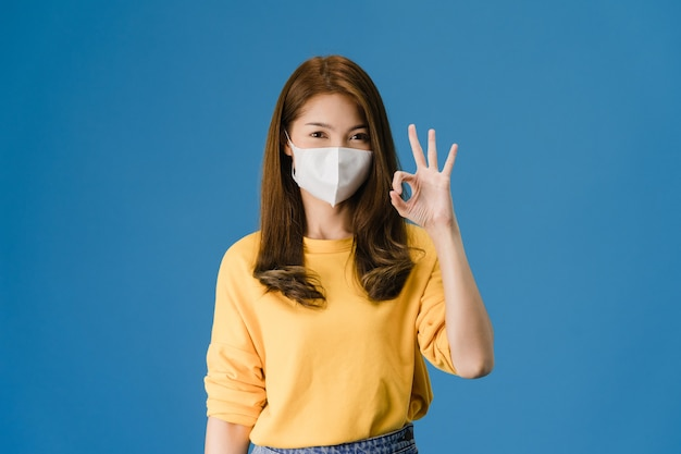 Young asia girl wearing medical face mask gesturing ok sign with dressed in casual cloth and look at camera isolated on blue background. self-isolation, social distancing, quarantine for corona virus. Free Photo