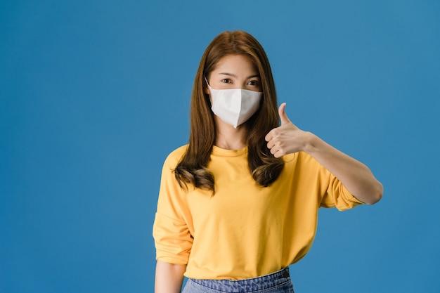 Giovane ragazza asiatica che indossa la maschera facciale medica che mostra il pollice in su con vestito in un panno casual e guarda la telecamera isolata su sfondo blu. autoisolamento, allontanamento sociale, quarantena per il virus corona. Foto Gratuite