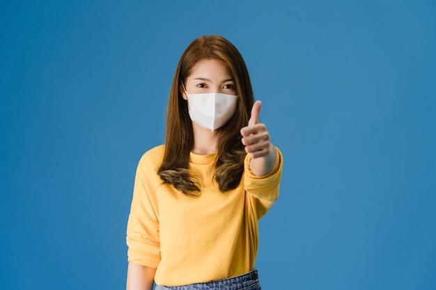 의료 얼굴 마스크를 착용하는 젊은 아시아 소녀 캐주얼 옷을 입고 엄지 손가락을 입고 파란색 배경에 고립 된 카메라를 봐. 자가 격리, 사회적 거리두기, 코로나 바이러스 격리. 무료 사진