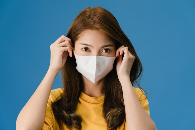 Young asia girl wearing medical face mask with dressed in casual clothing and looking at camera isolated on blue background. self-isolation, social distancing, quarantine for corona virus prevention. Free Photo