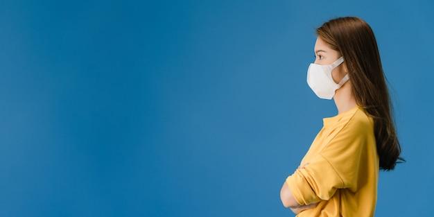 의료 얼굴 마스크를 착용하는 젊은 아시아 소녀 캐주얼 옷을 입고 파란색 배경에 고립 된 빈 공간을 봐. 코로나 바이러스에 대한 사회적 거리두기, 격리. 파노라마 배너 배경입니다. 무료 사진