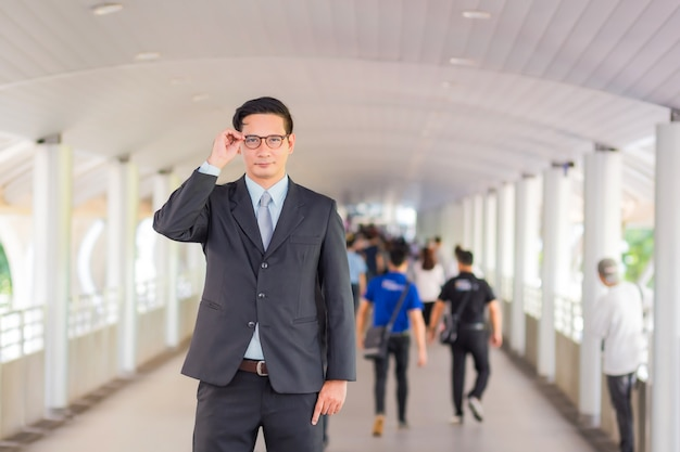 Young asia handsome businessman with his glasses standing on walkway of modern city. Premium Photo