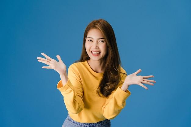 긍정적 인 표현, 즐겁고 흥미 진진한, 캐주얼 천을 입고 파란색 배경에 고립 된 카메라를보고 행복을 느끼는 젊은 아시아 아가씨. 행복 한 사랑스러운 기쁜 여자는 성공을 기뻐합니다. 무료 사진