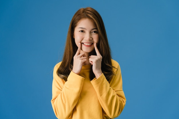Young asia lady showing smile, positive expression, dressed in casual cloth and look at camera isolated on blue background. happy adorable glad woman rejoices success. facial expression concept. Free Photo