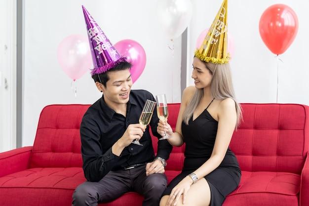 大都市の大きなマンションのリビングルームで一緒にスパークリングワインで誕生日を祝っている若いアジア大人カップル Premium写真