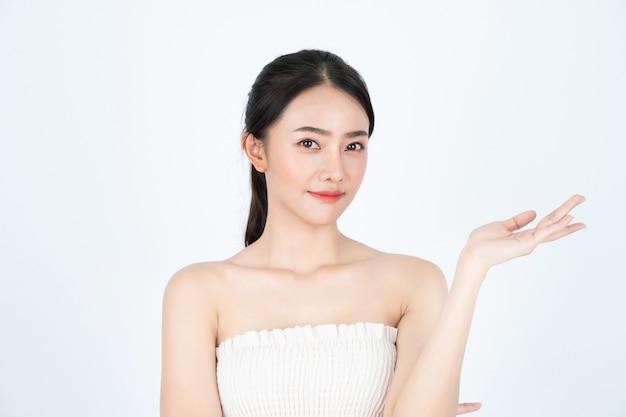 흰색 땀받이에 젊은 아시아 아름다운 소녀, 건강하고 밝은 피부, 제품을 제시했다. 프리미엄 사진