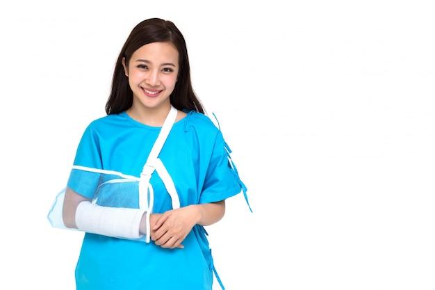 Костюмы молодой азиатской красивой женщины нося терпеливые и надели мягкое занавес из-за сломленной изолированной руки, концепции личной аварии Premium Фотографии