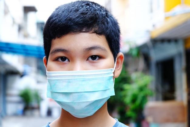細菌、有毒ガス、埃を防ぐためにマスクを身に着けている若いアジアの少年。細菌感染の防止コロナウイルスまたはcovid 19。 Premium写真