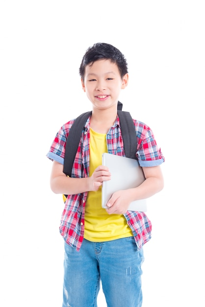 Young asian boy with backpack holding laptop computer and smiles over white background Premium Photo