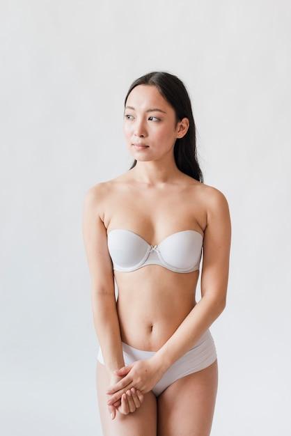 브래지어와 흰색 배경에 대해 속옷에 젊은 아시아 갈색 머리 무료 사진